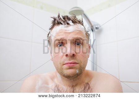Worried caucasian foamed young man after the water in the shower was turned off, looking at the camera. Shower breakdown or hot water shut-off.