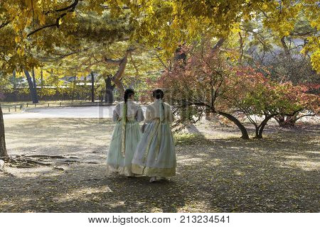 Asian girls with Hanbok(traditional Korean dress) and yellow autumn maple leaves in Gyeongbokgung palace in Seoul South Korea.