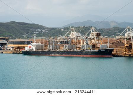 NOUMEA, NEW CALEDONIA, PACIFIC ISLANDS-NOVEMBER 25TH, 2016: Cargo ship moored at commercial dock with island landscape under an overcast sky in Noumea, New Caledonia