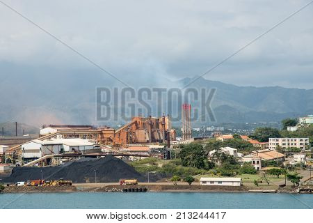 NOUMEA, NEW CALEDONIA, PACIFIC ISLANDS-NOVEMBER 25TH, 2016: SLN plant on the Pacific Ocean waterfront with smoke stacks, island landscape and cloudy skies in Noumea, New Caledonia