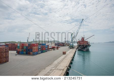 NOUMEA, NEW CALEDONIA, PACIFIC ISLANDS-NOVEMBER 25TH, 2016: Commercial port with shipping containers, nautical vessel and cranes under an overcast sky in Noumea, New Caledonia
