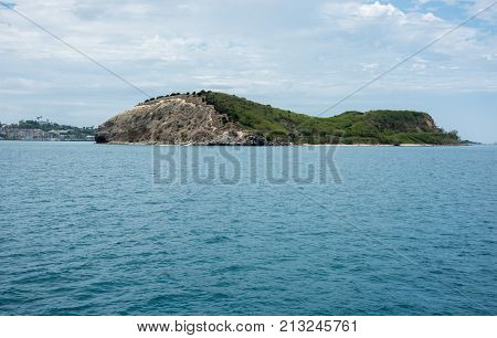 Coastal island feature with lush greenery and natural rock formations in Noumea, New Caledonia