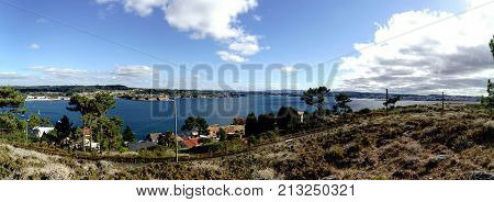 Panoramic View Of The Coast Of La Coruna Bay With A Blue Sky And Clouds Receiving The Reflection Of