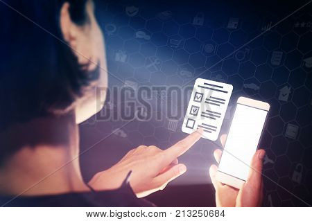 Image of a girl with a smartphone in hands. She presses on the questionnaire icon. Concept of online testing questionnaires voting.
