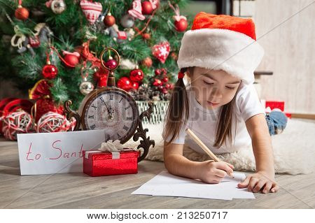Little girl in Santa hat writes letter to Santa Claus near christmas tree