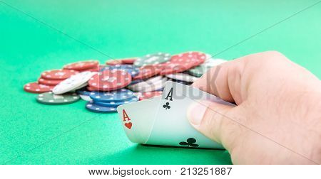 Male hand show pair of aces on the green poker table.