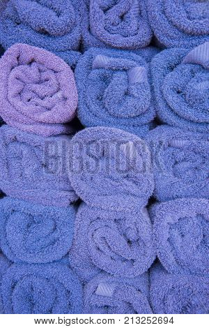 Full frame background of rolled purple towels stacked.