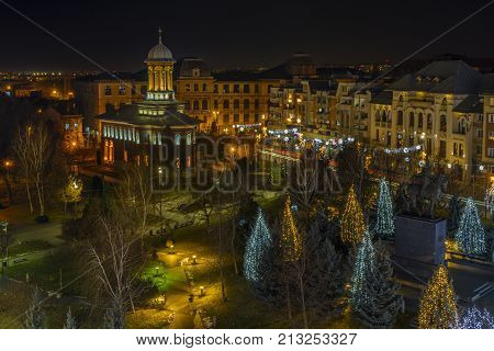 Night view with Holy Trinity Church the statue of Michael the Brave Christmas lights and decorated trees in the 2nd day of Christmas on December 27 2016 in the central park in Craiova Romania.