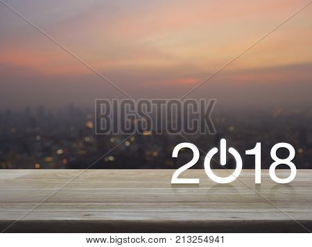 2018 start up business icon on wooden table over blur of cityscape on warm light sundown Happy new year concept