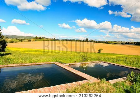 Tuscan landscape in spring with a fountain and hills