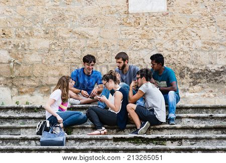 SAN GIMIGNANO ITALY - JUNE 11 2016 - A multi-ethnic group of guys having fun chatting on the stairs of a church in a square in San Gimignano in Tuscany