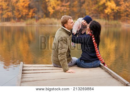 young parents sitting on wooden bridge and play with little daughter autumn forest and river on the background. Mom holding baby girl in hands. Happy family, parental love, autumn season concept