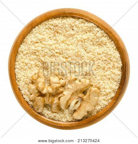 Ground walnuts and walnut kernel halves in wooden bowl. Walnut meal, used in bakery. Grounded kernels. Seeds of the common walnut tree, Juglans regia. Macro food photo close up from above over white.