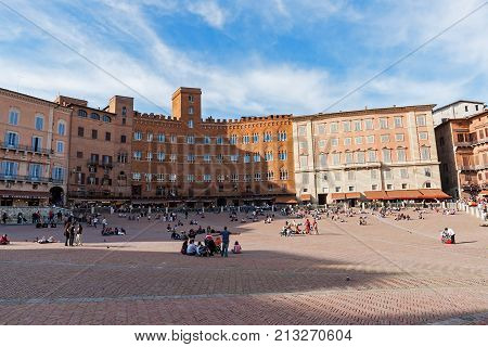 Siena Italy - May 10 2008: Unidentified tourists sunbathing on Piazza del Campo in Siena. Piazza del Campo is the principal public space of the historic center of Siena.