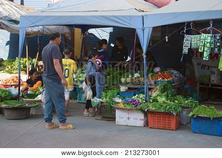 SUKHOTHAI, THAILAND - DECEMBER 29, 2016: Thai family buys vegetables on the city market