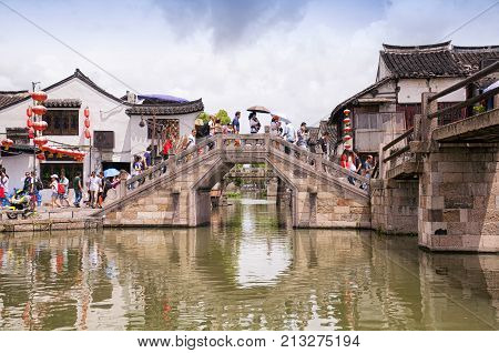August 8 2015. Xitang Town China. Chinese and western tourists crossing a stone bridge in the Xitang water town located in in Jiashan County in Jiaxing City Zhejiang Province china.