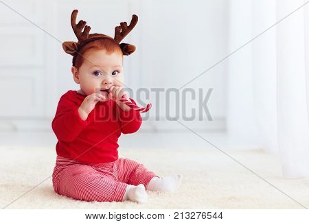 Cute Little Redhead Baby Boy With Reindeer Band Tasting Christmas Sweet Treats, Sitting On The Floor