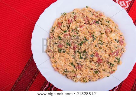 Traditional Bulgarian vegetable dish mish mash with mixed baked peppers, tomatoes, cheese, onion and scrambled eggs.