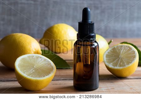 A Bottle Of Lemon Essential Oil With Lemons