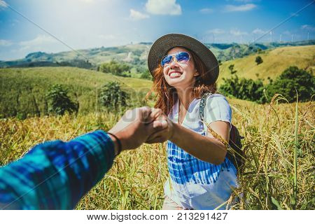 Lover women and men asians travel relax in the holiday. Lovers walk hand in hand on field. Thailand
