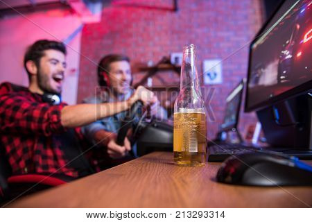 Playful mood. Low angle close-up focus bottle of light beer is on computer table. Joyful young gamers with headphones are playing car racing video game using steering wheel in background