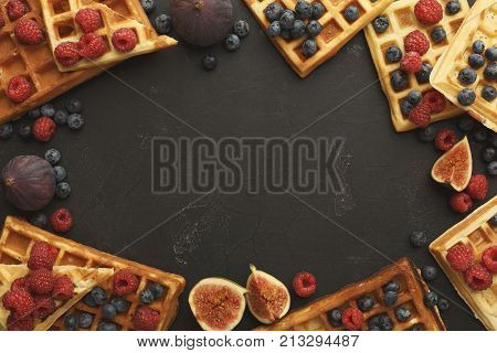 Belgium waffles with berries and figs on black background. Border of checkered biscuits top view with copy space. Sweet food and tasty breakfast concept