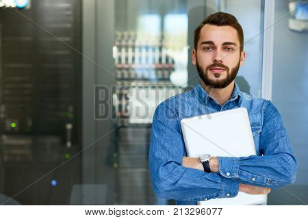 Portrait of beraded systems administrator posing holding laptop and looking at camera standing against server cabinet, copy space
