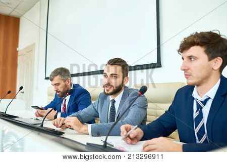 Portrait of several business people sitting in row participating in political debate during press conference answering media questions, bearded man speaking to microphone