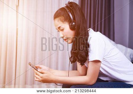 Woman Listening To Music In Headphones With Moblie On Sofa At Home