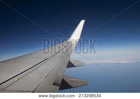 Wing of an airliner plane in flight. Blue sky. A wing of a passenger jet airbus. During the flight. In cruising altitude. poster