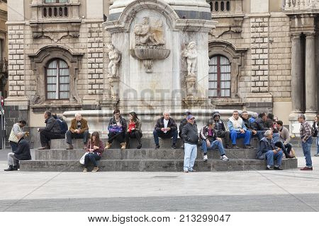 CATANIA, ITALY. April 03, 2015: Piazza del Duomo main city square in Catania, Sicily. Italy. Obelisk with elephant (Symbol of the city). On the steps of the monument many people, citizens and tourists