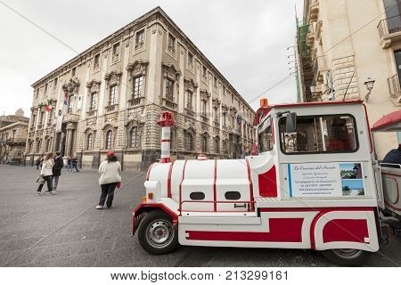 CATANIA, ITALY. April 3, 2015: Small white train wagon sightseeing for tourists and historic buildings in the city center of Catania in Sicily, Italy.