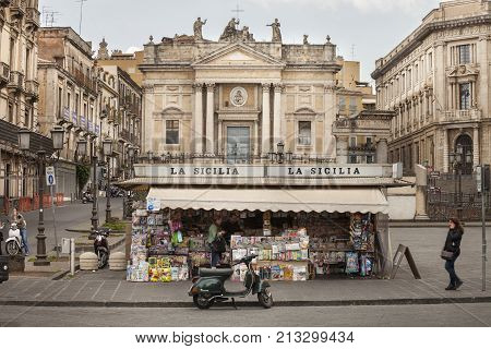 CATANIA, ITALY. April 03, 2015: The historic center of Catania, Sicily. Newsstand on the square (Piazza Stesicoro) with views of the Roman amphitheater and the church of San Biagio.