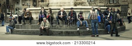 CATANIA, ITALY. April 03, 2015: People sitting on the steps in the Square (Piazza) del Duomo in Catania city center, Italy.