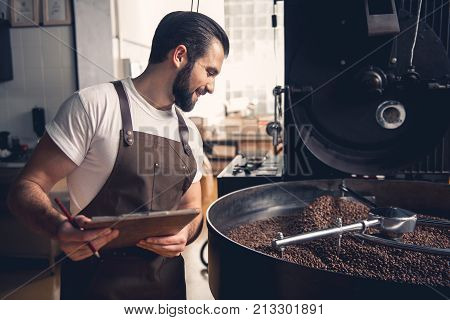 Side view happy unshaven worker noting about preparing coffee grains in appliance. Check concept