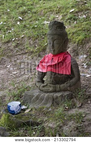 Nara - Japan, May 30, 2017: Traditional stone carved Jizo with red skirt honored and respected with a cup of water