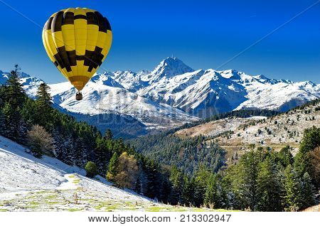 black and yellow hot air balloon with Pic du Midi de Bigorre in the french Pyrenees
