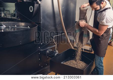 Side view outgoing bearded male worker pouring coffee beans in case. Prepare concept