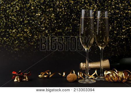 Celebrating new year, birthday, xmas party. Bottle of champagne, flutes and colorful tinsel on black backgroud with golden glitters, copy space. Mockup for postcard