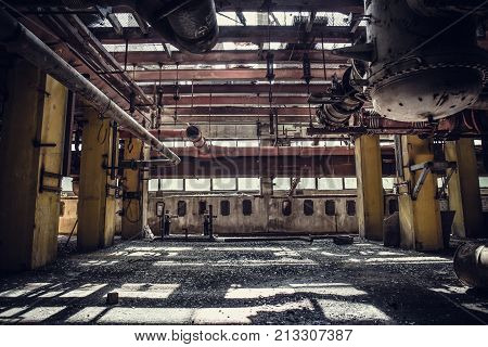 Abandoned metallurgical excavator plant or factory interior, industrial warehouse building waiting for a demolition, toned