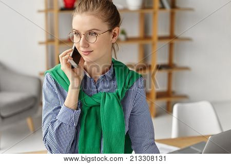 Creative Female Designer Sits At Her Cabinet, Looks Pensively Aside, Calls Family To Say That She Is