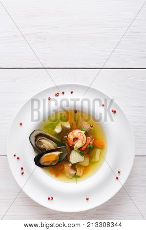 French cuisine restaurant. Seafood soup with white fish, shrimps and mussels in plate sprinkled with spices. Freshly cooked exclusive meals at white wooden background with copy space, top view