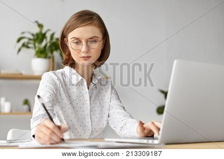 Indoor Shot Of Serious Concentrated Business Lady Dressed Formally, Writes In Notebook, Searches Int