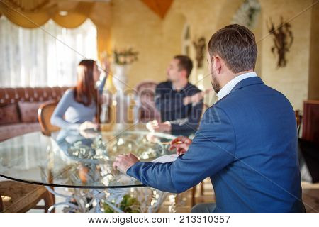 At the psychologist. A young couple is sitting at the table, swearing, the girl is waving her hands, the doctor is sitting in the chair, taking notes.