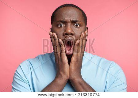 Headshot Of Stupefied Astonished Black Plump Man Wears Casual T Shirt, Keeps Hands On Cheeks, Says: