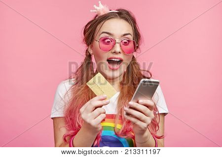 People And Technology Concept. Adorable Cute Chick Girl Holds Credit Card And Modern Mobile Phone, T