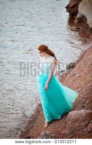 beautiful young girl with red hair in a lavish dress walking in the nature near the lake