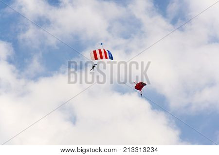 Two Parachutists Skydiving With Colorful Parachute Clouds Blue Sky Background
