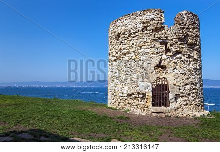 NESSEBAR BULGARIA - SEPTEMBER 11 2017: The old watchtower of the ancient Bulgarian town Nessebar on the background of the resorts Sunny Beach.