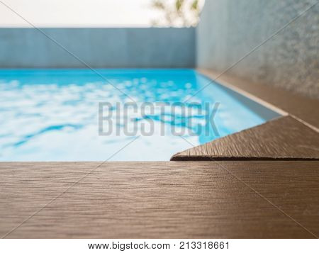 blue swimming pool with artificial wood deck